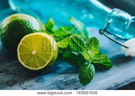 Mint leaves, lime and glass bootle  on wooden tray.