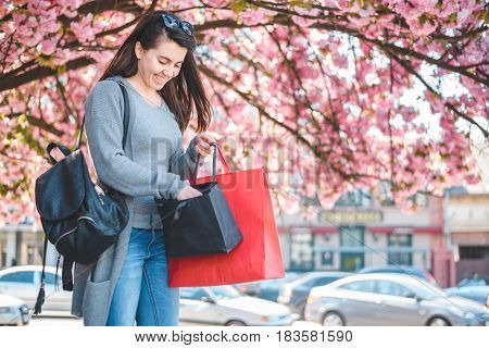 happy girl looknig into shopping bags, blooming sakura on background