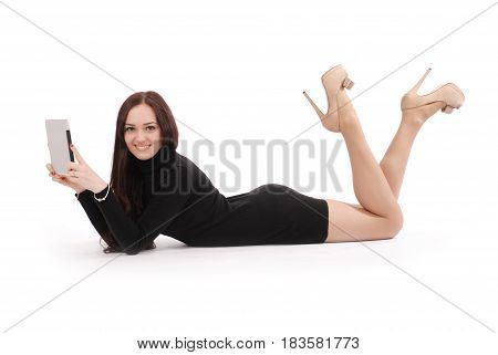 Teenage girl lying on the floor with tablet pc isolated on white