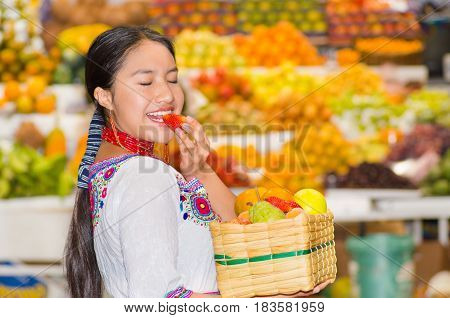Beautiful young hispanic woman wearing andean traditional blouse posing for camera holding basket of fuits, putting strawberry in mouth, inside fruit market, colorful healthy food selection in background.