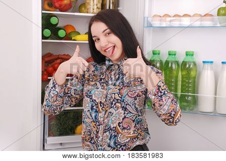 Satisfied housewife near filled fridge. Beautiful young girl near the fridge.