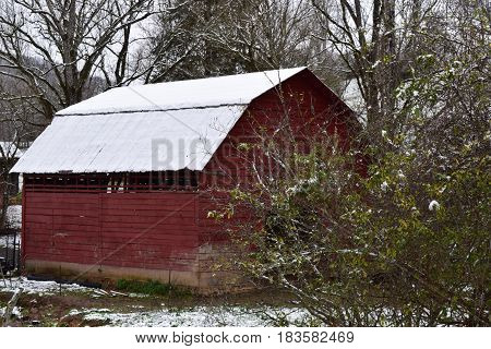 Red barn in early Spring with a dusting of snow on the roof.