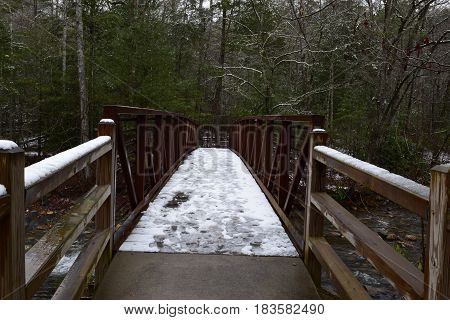 Metal foot bridge over a creek during early Spring with a dusting of snow.