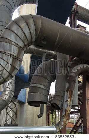 Old industrial technological installations with damaged pipelines and pipes