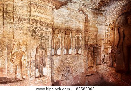 Indian rock-cut architecture. Carved wall dedicated to revered figures of Jainism inside the 7th century cave temple in town Badami, India.