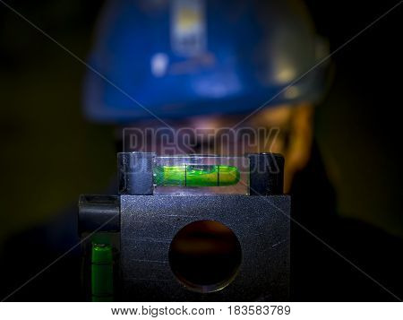 construction worker checking spirit level or bubble level in a dark place