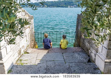 boys sitting on a dock looking at the beautiful lake garda in italy