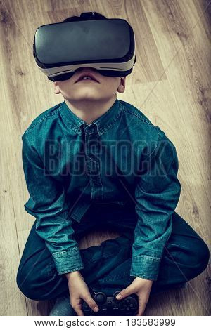 boy playing virtual reality games on the floor