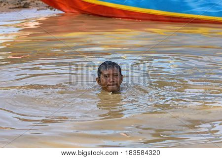 Tonle Sap lake, Cambodia - January 04, 2017: View of a fisherman immersed in water. About 80,000 people live on the lake's water permanently, and fishing is the main source of income