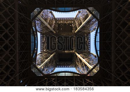 A picture of Eiffel tower from below, showing its complex and magestic architecture.