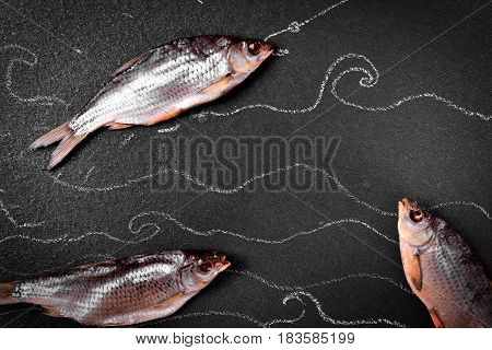 Three dried in the salt fish ram on the black surface chalk painted sea waves