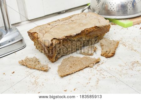 Crushed bread of your own baking on the kitchen counter. Failed baking home made bread.