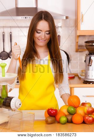 Woman In Kitchen Preparing Fruits For Juicing