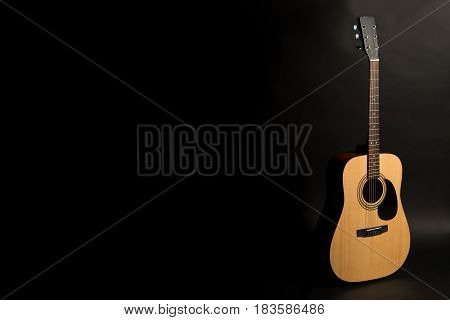 Acoustic Guitar On A Black Background On The Right Side Of The Frame, Half-turn. Stringed Instrument