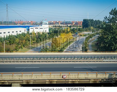 Tianjin, China - Nov 1, 2016: Image captured on High Speed Rail (HSR) from Tianjin to Shanghai, passing countryside with new roads around an industrial area. Average speed: 300 km/hr.