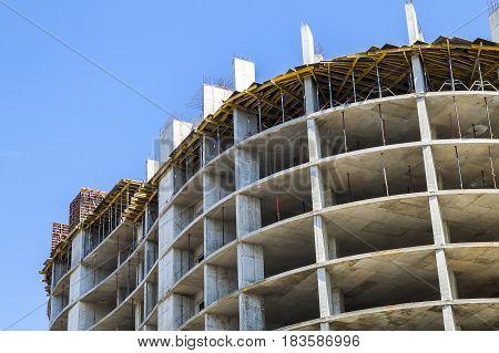 Modern Building Under Construction Against Blue Sky. Construction Work Site