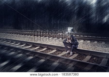 Sad man sitting on the rails in depresion, cry
