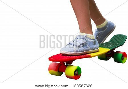Adorable toddler boy having fun with colorful skateboard isolate