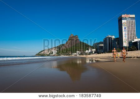 Rio de Janeiro, Brazil - April 6, 2017: Mountains reflecting in water of Leblon beach. Leblon is Latin America's most expensive land.