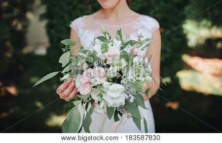 A beautiful wedding bouquet in the hands of the bride.