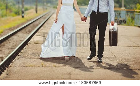 Young loving couple with suitcase on a railway station.