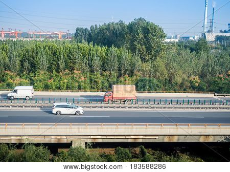 Tianjin, China - Nov 1, 2016: Image captured on High Speed Rail (HSR) from Tianjin to Shanghai, passing countryside with vehicles moving on road around an industrial area. Average speed: 300 km/hr.