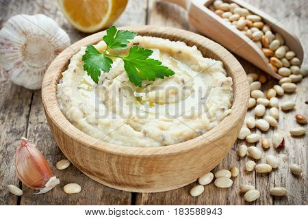 White beans hummus with lemon garlic and flax in wooden bowl traditional arabic cuisine