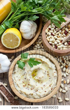 White beans hummus with lemon garlic and flax on a wooden background with ingredients