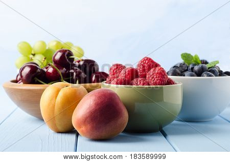 Fresh Fruit Choices In Bowls On Light Blue Wood Planked Table