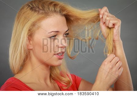 Haircare health problem concept. Unhappy sad woman looking at damaged split ends on her blonde hair