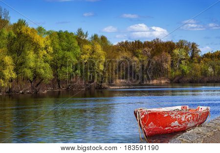 Red old boat anchored by the river bank over stunning autumnal river scape