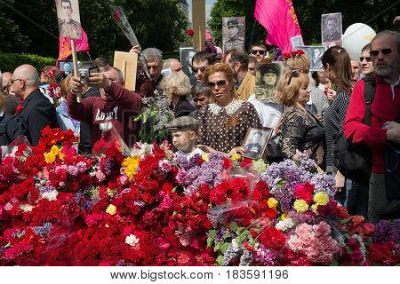 Kiev Ukraine - May 09 2016: Participants of the action Immortal regiment with portraits of dead relatives - soldiers lay flowers at the memorial of an unknown soldier