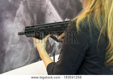 Girl with an automatic rifle in the hands of the counter. Weapons