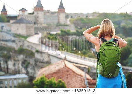 Woman tourist with green backpack makes a photo of an old castle. vacation and summer trip