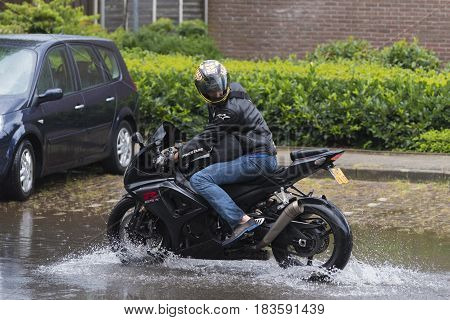 OLDENZAAL NETHERLANDS - JULY 21 2016: Unknown motor driver with his motor bike in a flooded street after a heavy rain
