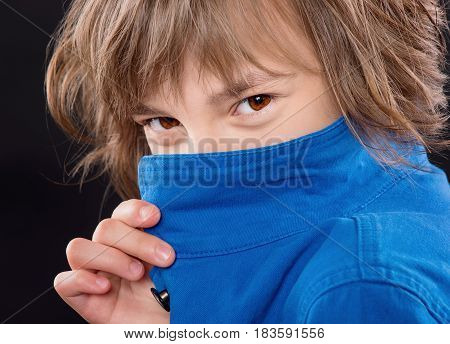 Little girl hides behind her blue collar. Close-up emotional portrait of attractive caucasian girl. Funny cute smiling child looking at camera on black background.