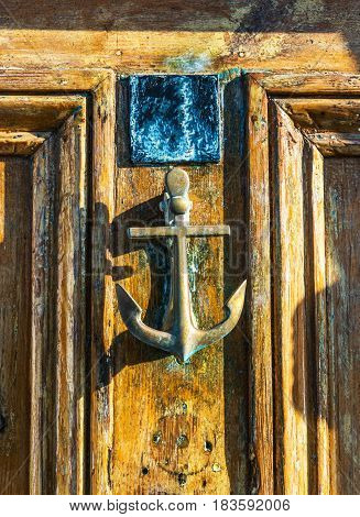 Old Wooden Door To House With Brass Knocker Shaped Like An Anchor, Sea Element