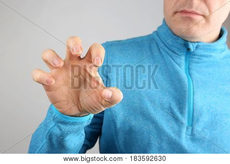 man demonstrates the nails on his right hand