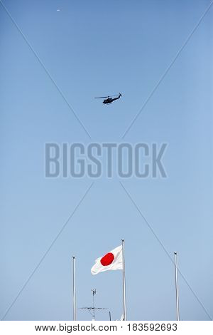 Japanese flag in wind with military helicopter