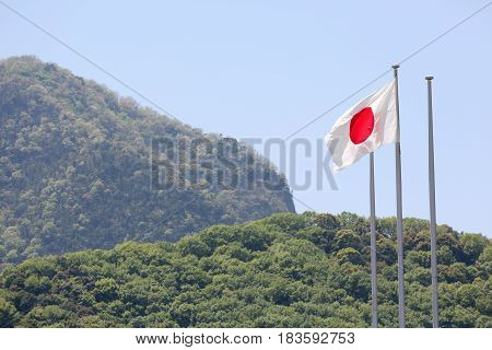 Japanese flag in wind against blue sky with mountain