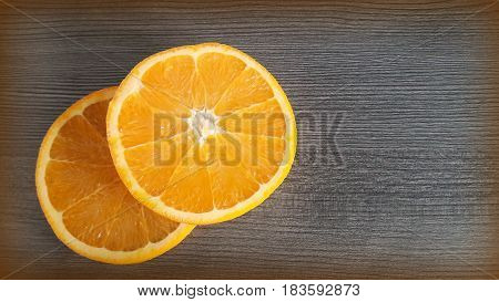Two orange slices on wooden background. Orange circle on wooden background.
