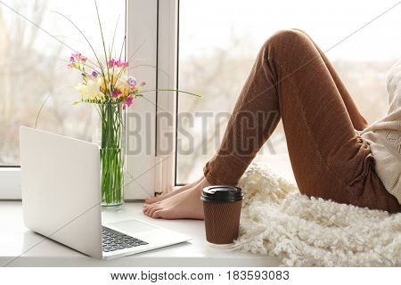 Beautiful young woman with laptop and cup of coffee sitting on window sill at home