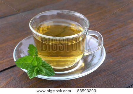 Glass cup of mint tea with mint leaves served outside on a wooden desk