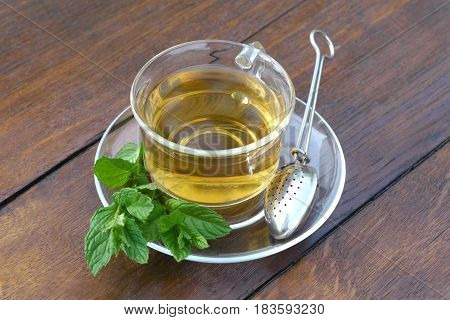 Glass cup of mint tea with mint leaves and tea holder spoon served outside on a wooden desk