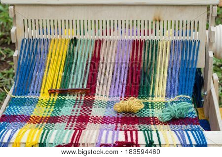 Colored threads in a wooden loom, on the market in Bashkiria