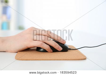 Hand of woman working with computer mouse in office