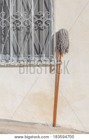 A mop stood outside a window of a house. Minimalist composition.