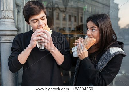 Young man and woman eating burgers with pleasure near cafe