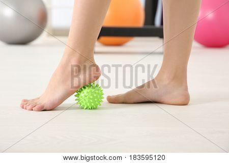 Feet of woman doing exercises with stress ball in clinic