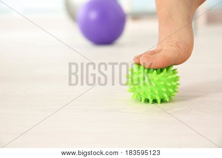 Foot of woman doing exercises with stress ball in clinic